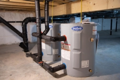 Two water heaters twinned together in crawl space